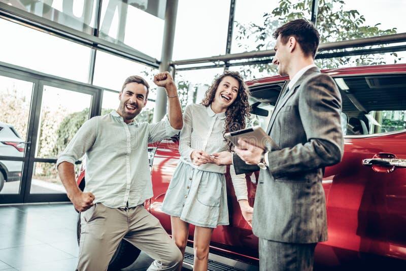 De verkoopsituatie in het autohandel drijven, de handelaar overhandigt autosleutels aan een jong paar, zijn zij opgewekt, auto's  royalty-vrije stock foto