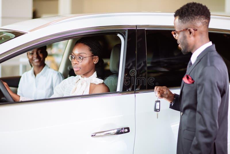 De verkoopsituatie in het autohandel drijven, jong Afrikaans paar krijgt de sleutel voor nieuwe auto royalty-vrije stock fotografie