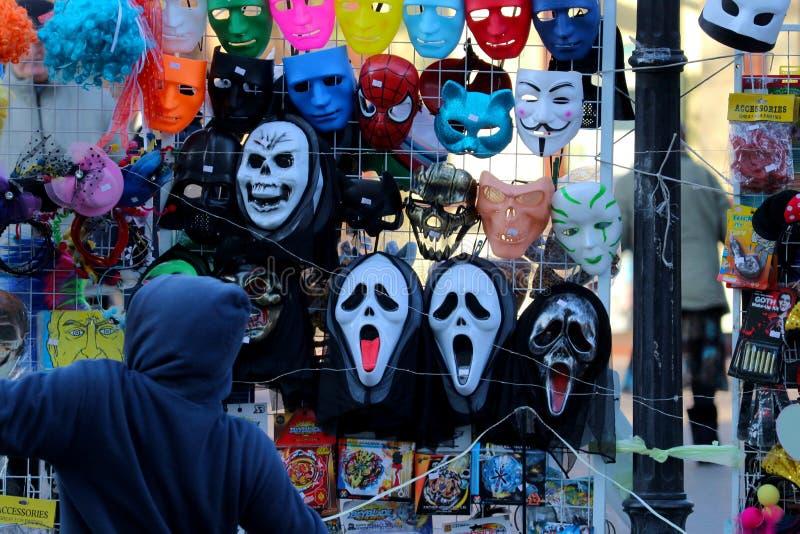 De verkoper bij het venster van het straatdienblad met maskers van 'Vete 'de van de film 'Schreeuw 'en anderen royalty-vrije stock afbeelding