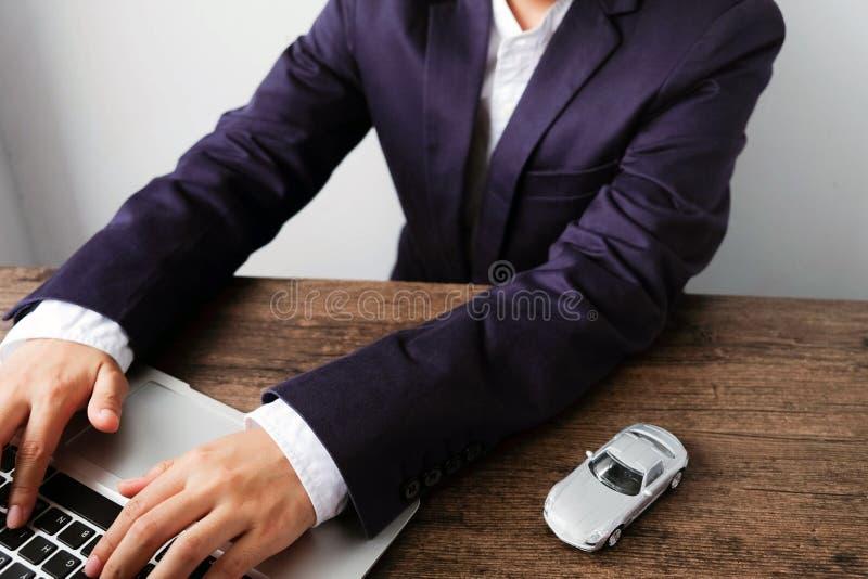 De verkoper registreert document op laptop met automodellen en n royalty-vrije stock fotografie