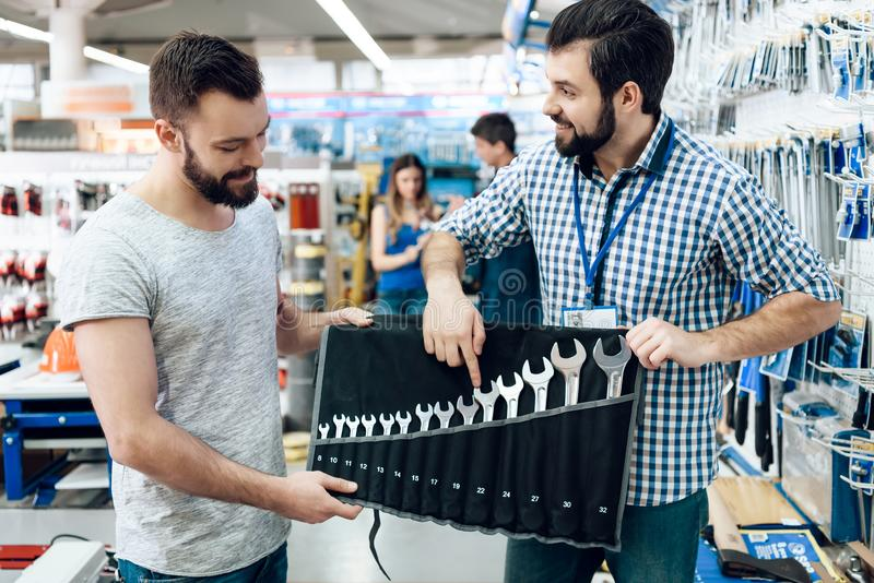 De verkoper toont gebaarde cliëntreeks moersleutels in de opslag van machtshulpmiddelen royalty-vrije stock foto