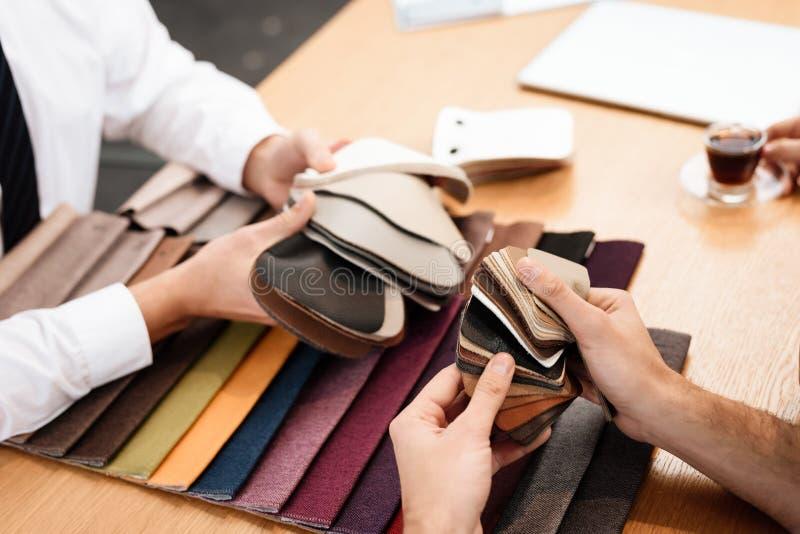 De verkoper toont steekproeven van materialen voor meubilair stock fotografie