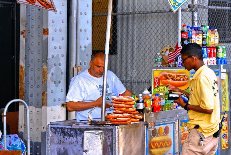 De verkoper van het straatvoedsel van hotdog, de pretzel en de dranken met costumier dichtbij Brooklyn overbruggen binnen de Stad royalty-vrije stock foto's