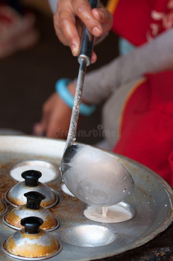 De verkoper van het straatvoedsel kookt pannekoek op de nachtmarkt van Luang Prabang stock afbeelding
