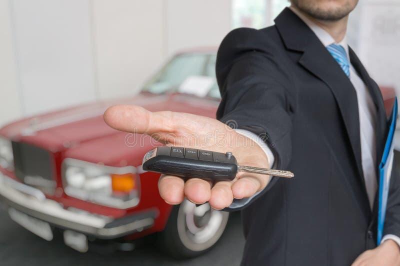 De verkoper verkoopt een nieuwe auto en gaat sleutels over stock afbeelding