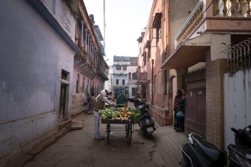 De verkoper verkoopt groenten en fruit van karren in de smalle straten van de oude Indische stad van Varanasi royalty-vrije stock foto's