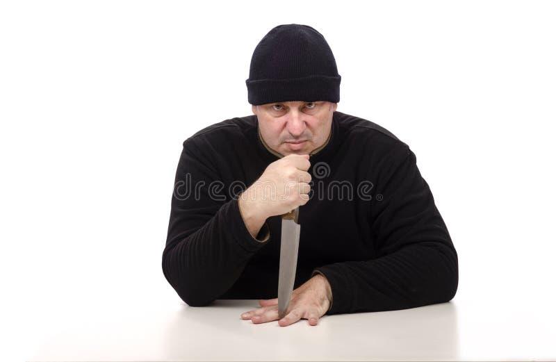 De verkrachter zit met groot mes stock foto's