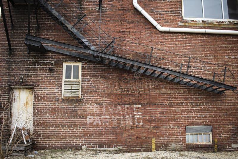 De verlaten baksteenbouw met metaaltrap stock fotografie