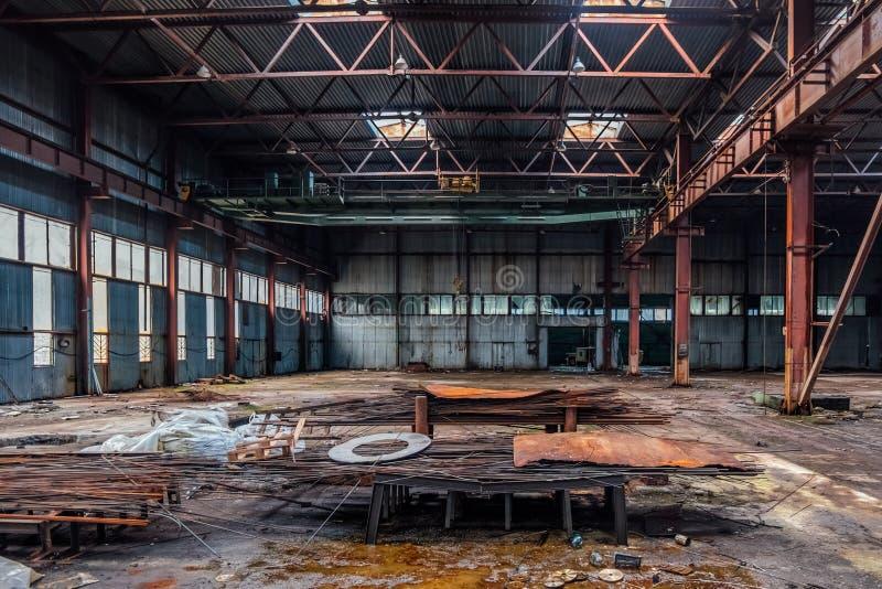 De verlaten industriële bouw met oude roestige brugkraan en metaalbouw stock foto's