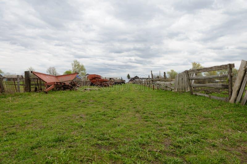 De verlaten landbouwmachines bevinden zich dichtbij oude houten omheiningen stock foto