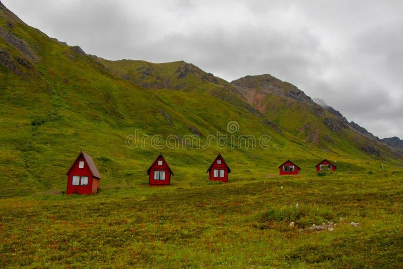 De verlaten rode cabines zitten in de groene weelderige bergen van de Pas van Alaska s Hatcher dichtbij Onafhankelijkheidsmijn, d royalty-vrije stock fotografie
