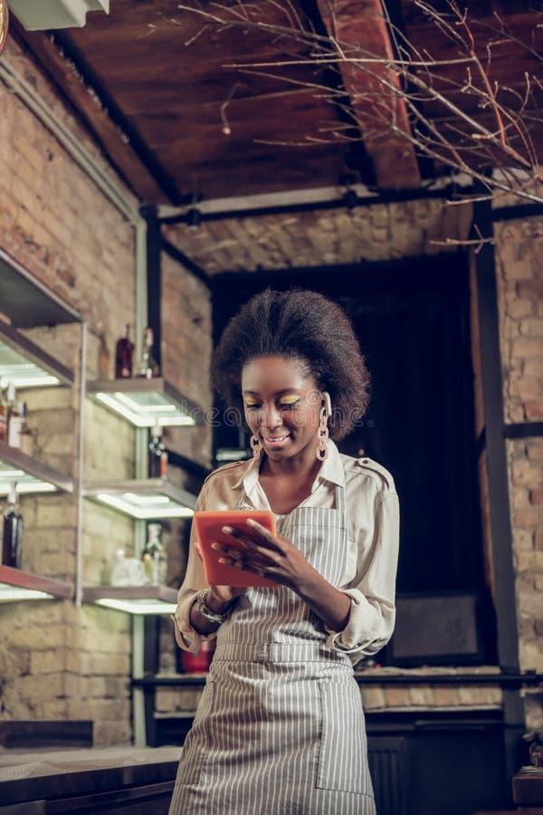 De verleidelijke Afro-Amerikaanse serveerster die van de zolderbar ordeinformatie zetten aan tablet stock foto's