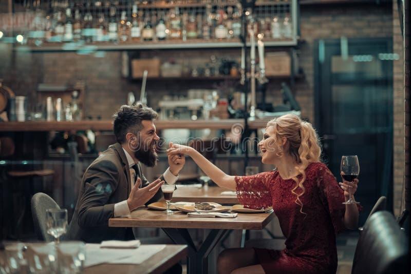 De verleiding van mooie vrouw die haar minnaar met wijnglas bekijken Het hebben van romantische bespreking stock afbeeldingen
