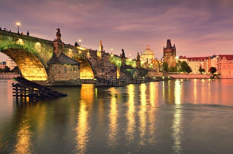 De verlichte Charles Bridge komt 's nachts tot uiting in de rivier Vltava in Praag royalty-vrije stock fotografie