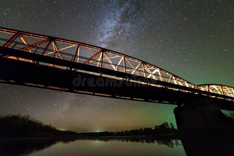 De verlichte metaalbrug op concrete steunen dacht in water op donkere sterrige hemel met de achtergrond van de Melkwegconstellati royalty-vrije stock foto's