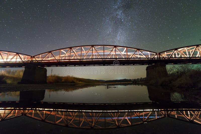 De verlichte metaalbrug op concrete steunen dacht in water op donkere sterrige hemel met de achtergrond van de Melkwegconstellati stock foto's