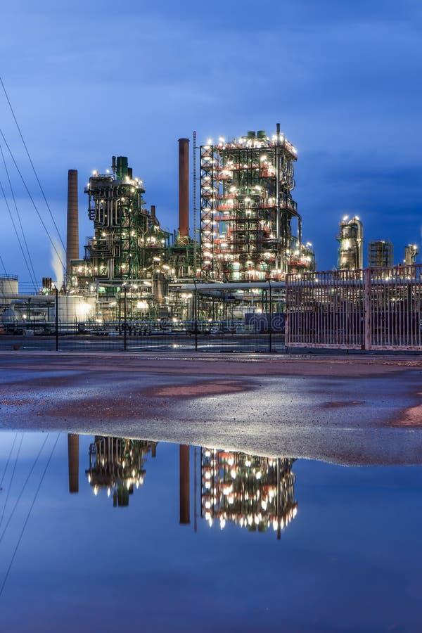De verlichte petrochemische productie-installatie bij schemering met dramatische wolken dacht in een vijver, Antwerpen, België na stock fotografie