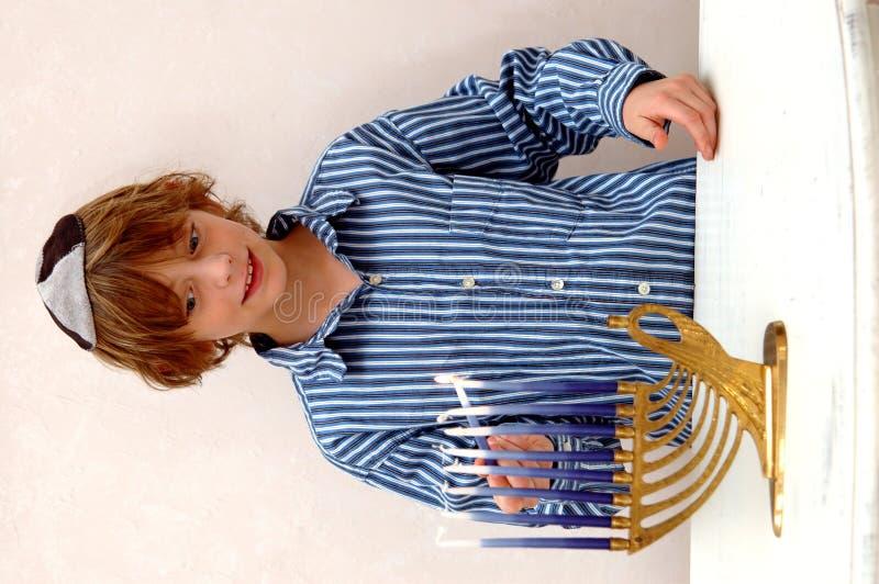 De verlichting Menorah van de jongen stock fotografie