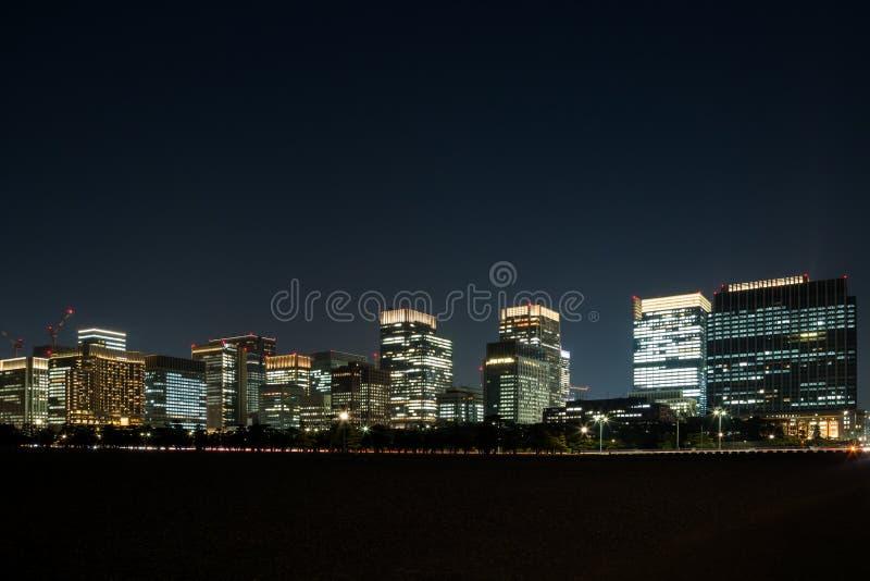 De verlichting van de stadsnacht van velen bouwen die waar bureaumensen die nog werken stock foto's