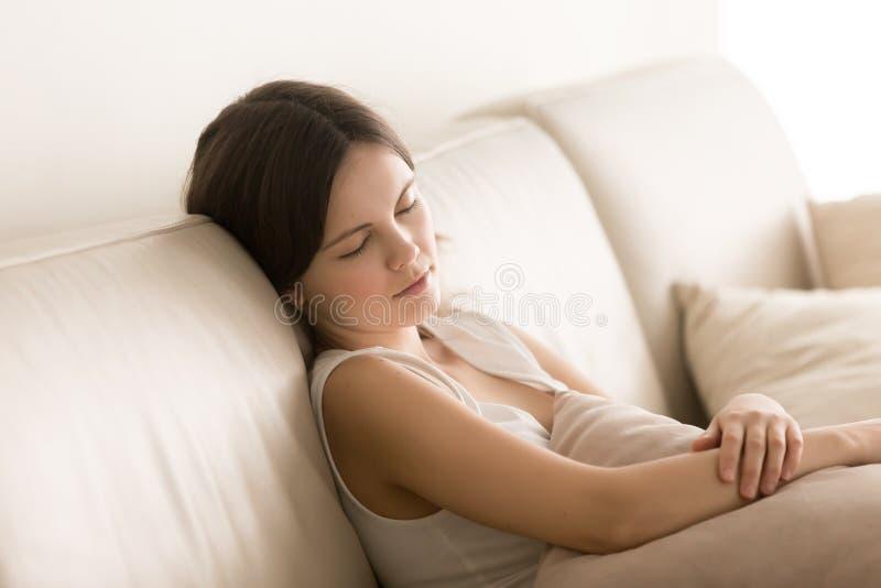 De vermoeide aantrekkelijke dame sluimert op comfortabele bank royalty-vrije stock afbeelding