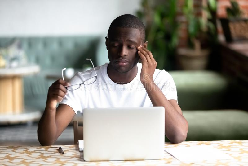 De vermoeide Afrikaanse Amerikaanse mens die glazen opstijgen, voelt oogspanning stock foto's