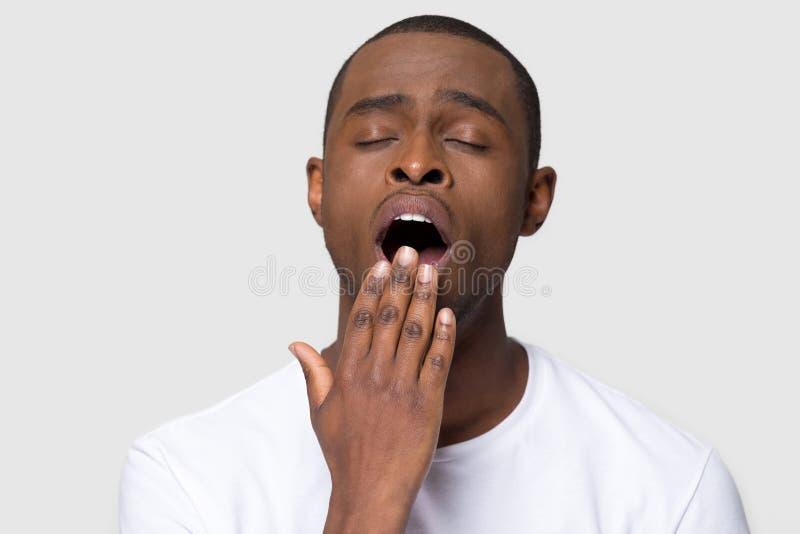 De vermoeide Afrikaanse mens mond van de geeuwdekking met het schot van de handstudio royalty-vrije stock afbeeldingen