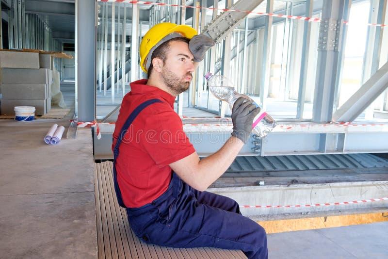 De vermoeide arbeider op bouwterrein heeft een onderbreking stock foto