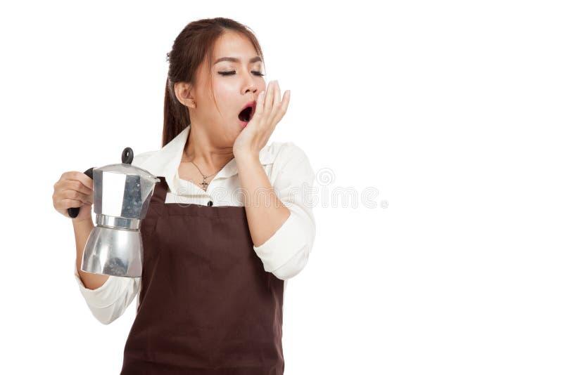 De vermoeide Aziatische geeuw van het baristameisje met de pot van koffiemoka royalty-vrije stock afbeeldingen