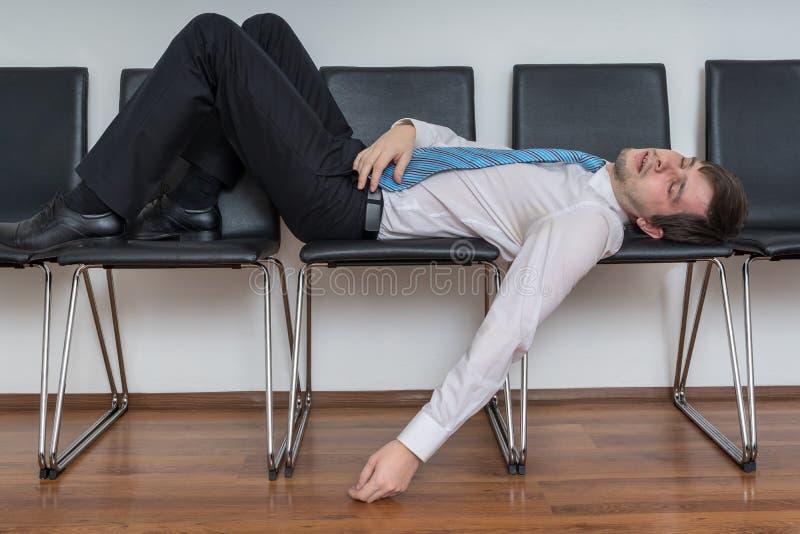 De vermoeide bored mens slaapt in wachtkamer op stoelen stock fotografie