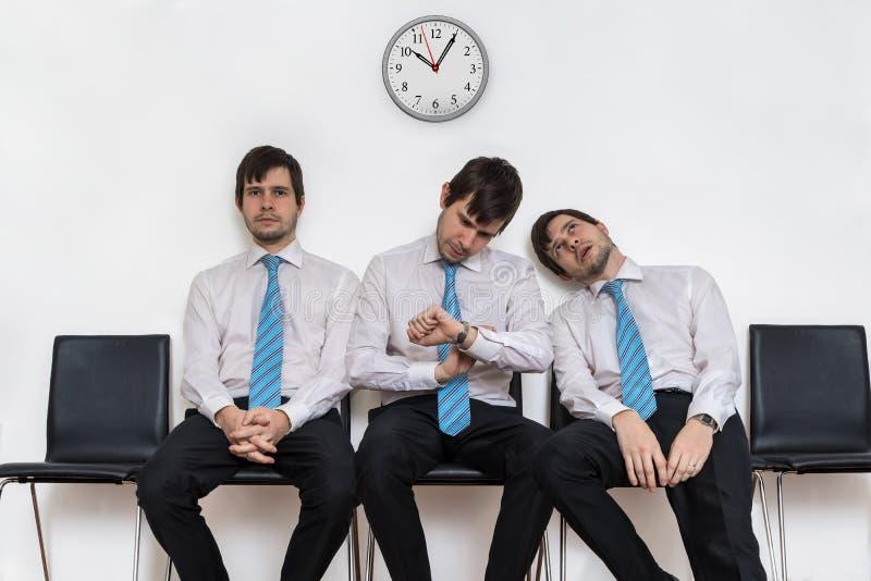 De vermoeide bored mens zit in wachtkamer op stoelen stock afbeeldingen