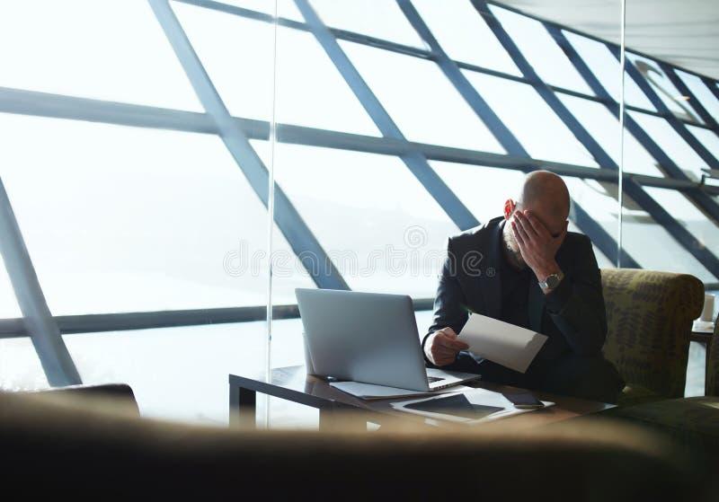 De vermoeide en gefrustreerde zakenman controleert de verklaringen van hun bedrijf stock foto's
