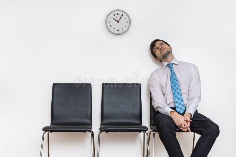 De vermoeide en uitgeputte mens zit in wachtkamer op stoel royalty-vrije stock foto's