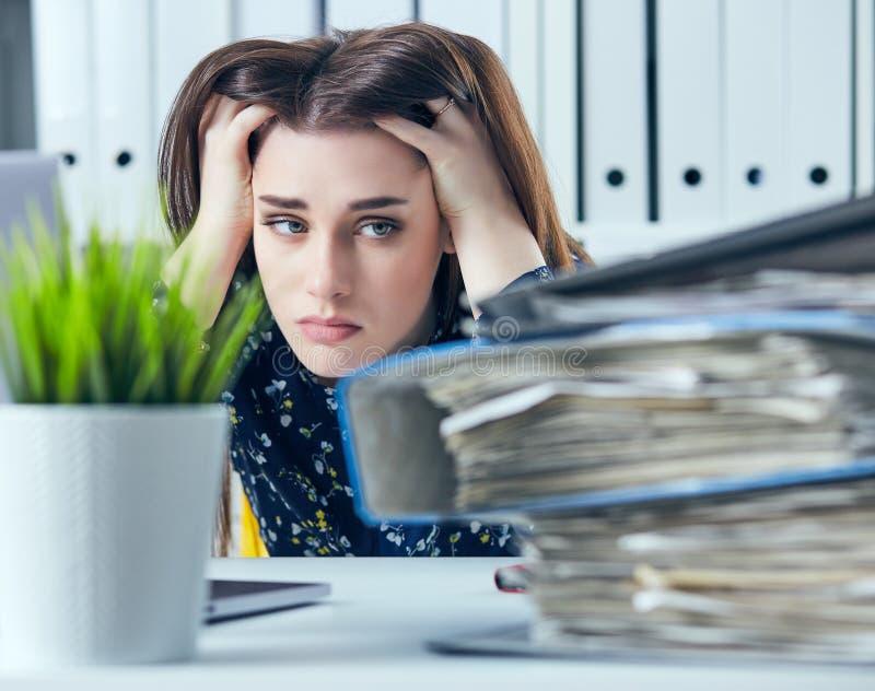 De vermoeide en uitgeputte vrouw in bril bekijkt de berg van documenten die omhoog haar hoofd met haar handen propping royalty-vrije stock foto