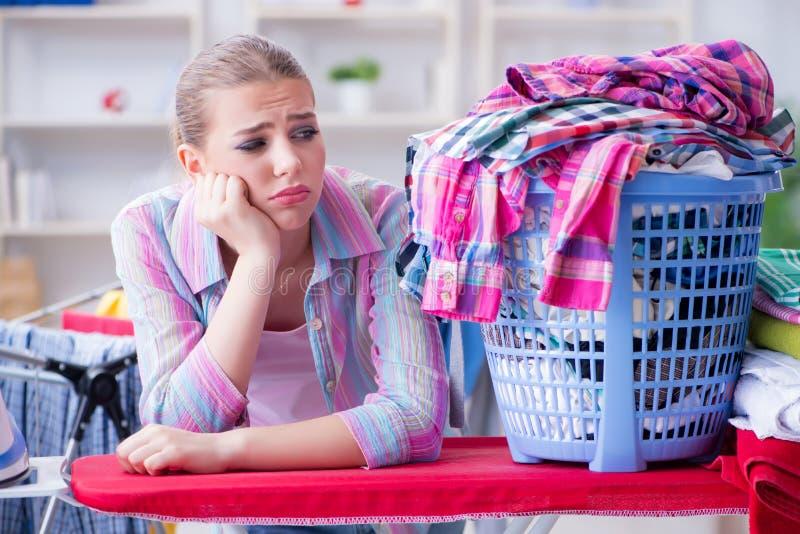 De vermoeide gedeprimeerde huisvrouw die wasserij doen