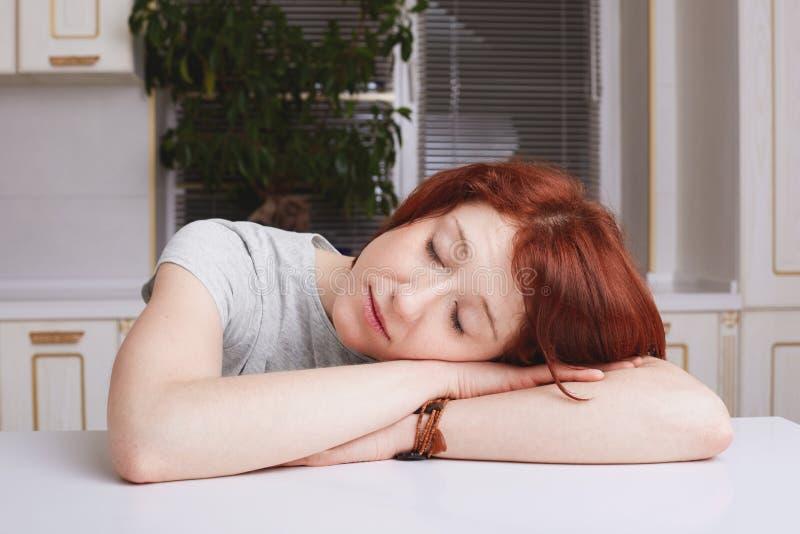 De vermoeide gemberhuisvrouw neemt dutje, leunt hoofd op handen, die moeheid na het schoonmaken van keuken, het sluitenogen, zit  stock afbeeldingen