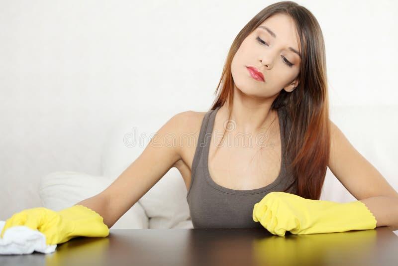 De vermoeide jonge lijst van het vrouwen schoonmakende meubilair royalty-vrije stock foto's