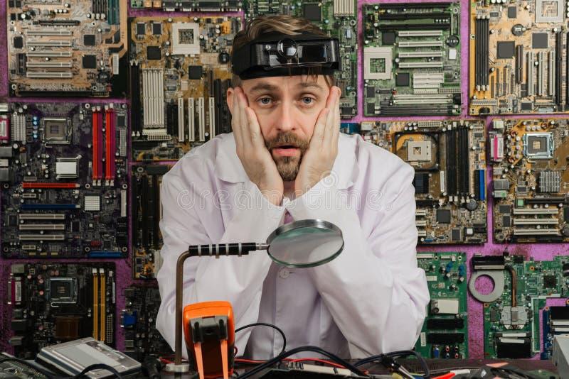 De vermoeide jonge mannelijke zitting van de elektricieningenieur bij de lijst van het elektrolaboratorium stock afbeeldingen