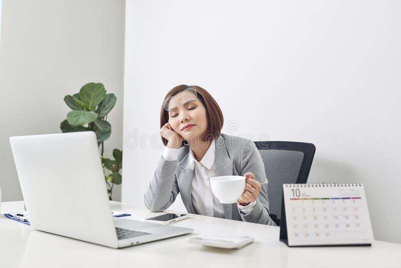 De vermoeide jonge onderneemster die een ogenblik bij haar bureau met haar ogen nemen te ontspannen sloot en hoofd die op haar ha stock foto
