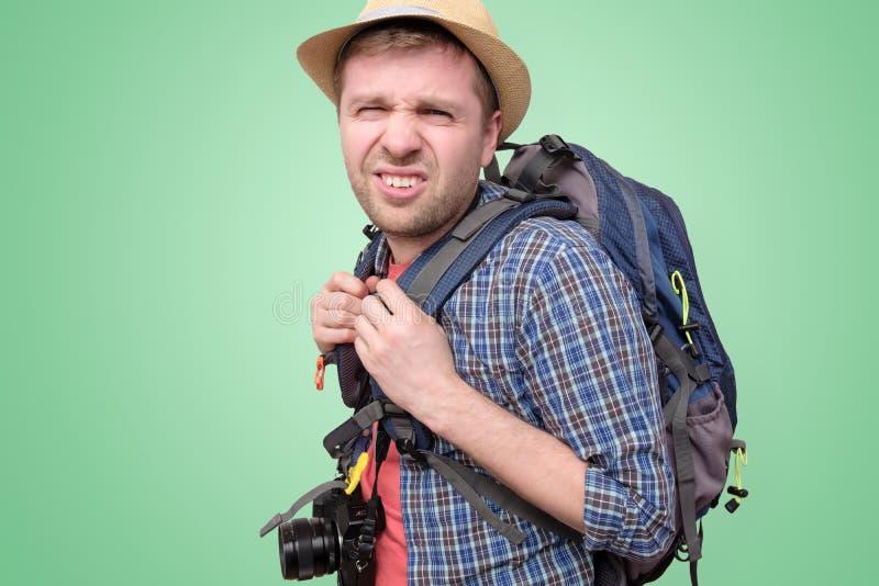 De vermoeide jonge toerist in de zomerhoed is vermoeid en verloren royalty-vrije stock foto's