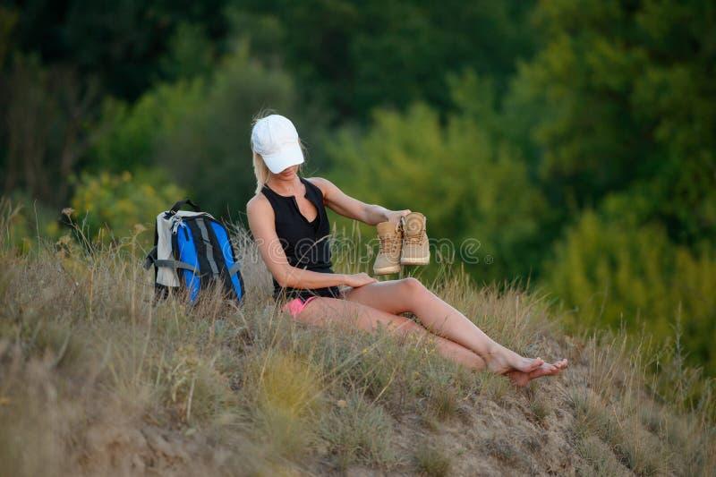 De vermoeide jonge zitting van de wandelaarvrouw op gras met in hand schoenen royalty-vrije stock afbeeldingen