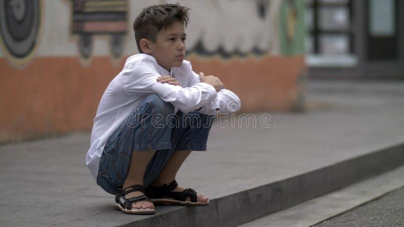 De vermoeide jongen zit in de straat, heeft pret royalty-vrije stock foto