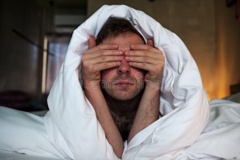 De vermoeide Kaukasische man legt op het bed en behandelt zijn gezicht met wapens royalty-vrije stock afbeeldingen