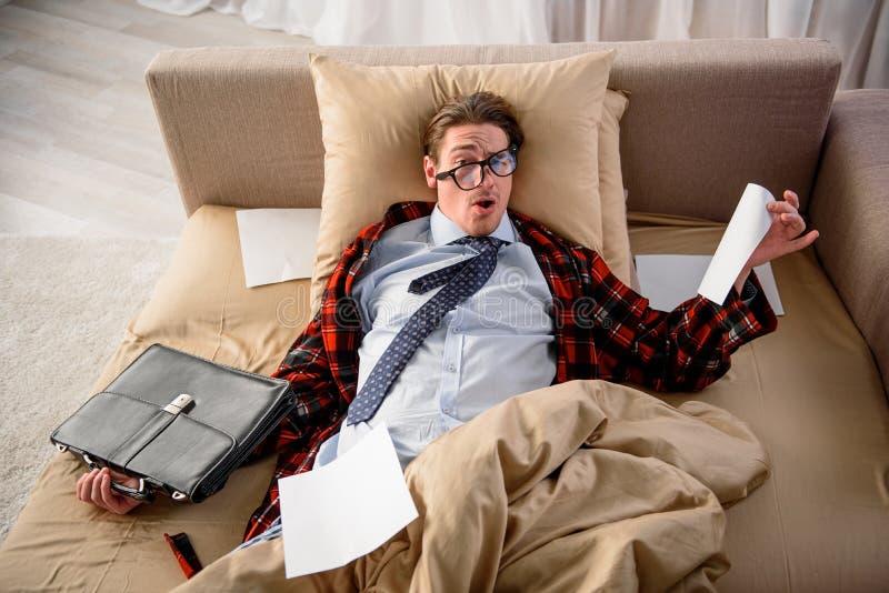 De vermoeide mens is tot oren in het werk bij slaapkamer royalty-vrije stock fotografie