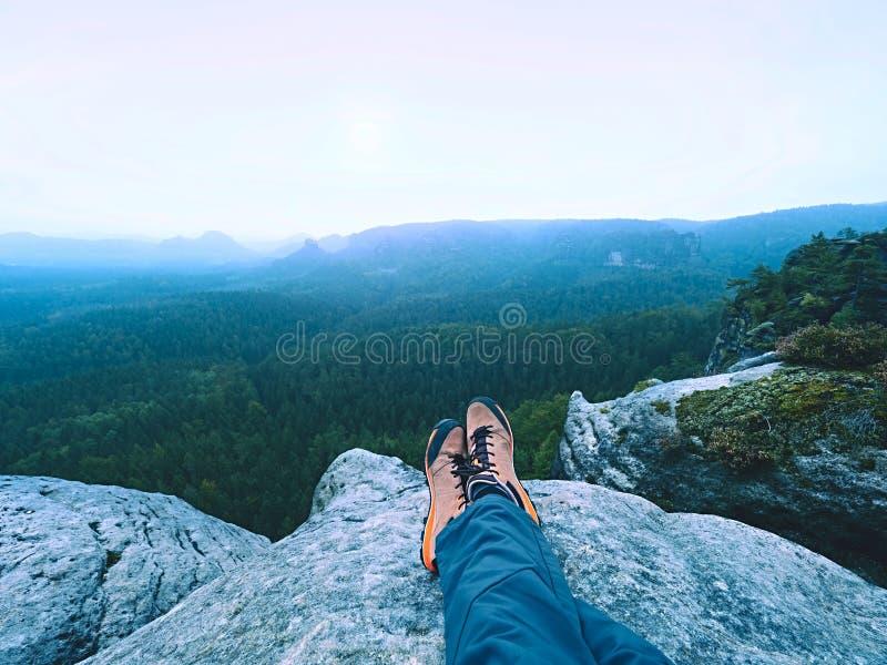 De vermoeide mensenwandelaar bepaalt en geniet van mening in landschap over zijn vermoeide benen in toeristenlaarzen stock foto's