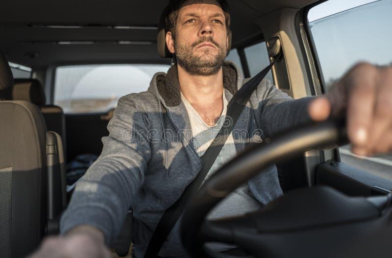 De vermoeide ongeschoren mens drijft auto stock foto