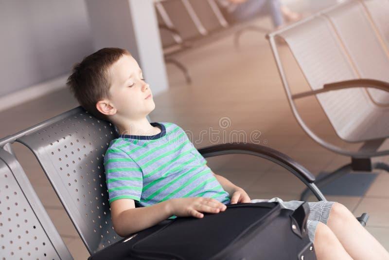 De vermoeide slaap van de kindjongen bij de luchthaven stock afbeelding
