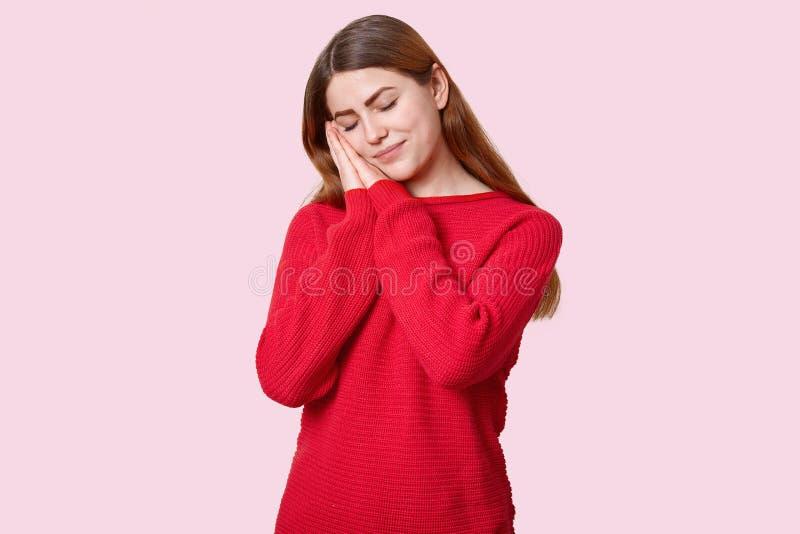 De vermoeide slaperige vrouw neemt dutje leunt op palmen, heeft gesloten ogen, gekleed in rode verbindingsdraad, wil rust hebben, stock foto