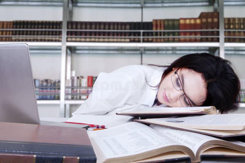 De vermoeide student viel een slaap in een bibliotheek royalty-vrije stock afbeelding