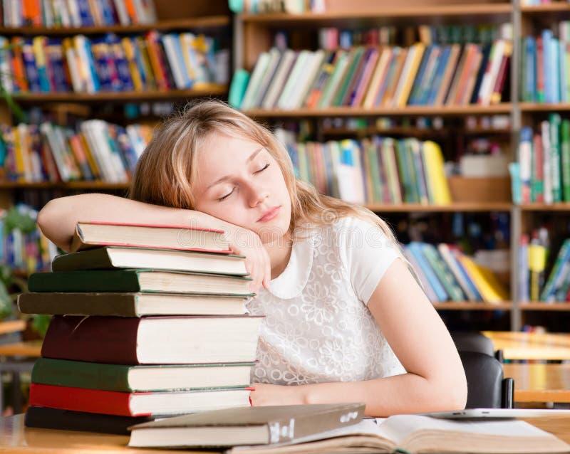 De vermoeide studentenslaap in bibliotheek op stapelboeken royalty-vrije stock foto