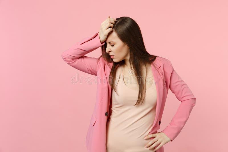 De vermoeide uitgeputte jonge vrouw die jasje draagt dat ogen houdt sloot het zetten van hand op verminderd hoofd dat op pastelkl stock afbeelding